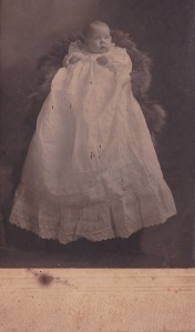 Detail of card photograph of Beth Wolf (or Half) in christening gown, made by Mr. & Mrs. Persons, Dublin GA ca. 1910