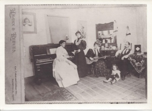 "A photograph from the studio of Hearn & Reeves; Beulah Reeves at the piano,  her sister Augusta Reeves standing near, their brother  Walter Roger Reeves seated, his wife Mary Tennessee ""Tennie"" Harrison Reeves with guitar, and their son   Charles Walton Reeves on the floor, about age five, ca. 1897; courtesy Ruth Reeves Dill"